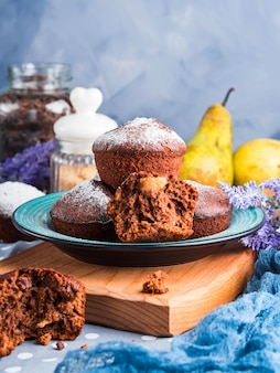 Chocolate muffins with pears and icing sugar