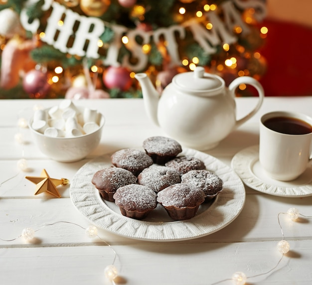 Chocolate muffins with tea  of christmas tree. xmas . greeting card and calendar template. christmas decoration. holiday dinner, sweet treats for kids.