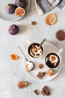 クリームチーズ入りチョコレートマグカップカップケーキまたは白いセラミックマグカップにキャラメルソースが付いたリコッタチーズ。秋または冬の食事を快適にします。