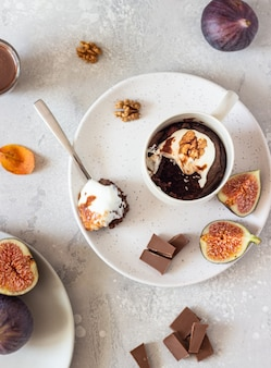 Chocolate mug cupcake with cream cheese or ricotta with caramel sauce in a white ceramic mug. comfort autumn or winter food.