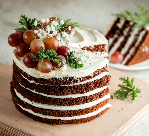 Chocolate naked cake decorated with white cream grapes and baby's-breath flowers