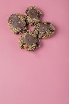 Шоколадное печенье с орехами на розовом столе.