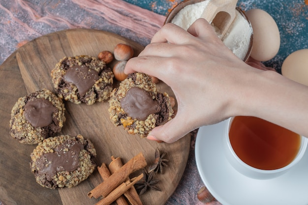 Chocolate nuts cookies on a wooden board served with cinnamons and a cup of tea.
