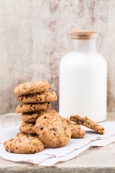 Шоколадное печенье обломока овсянки с молоком на деревенском деревянном столе.