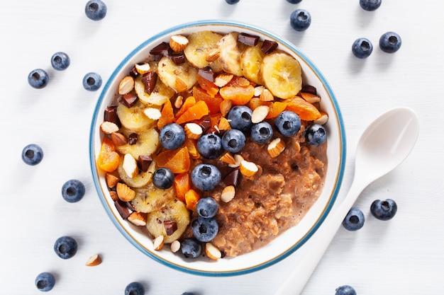 건강 한 아침 식사에 대 한 블루 베리, 견과류, 바나나, 말린 살구 초콜릿 오트밀 죽. 평면도