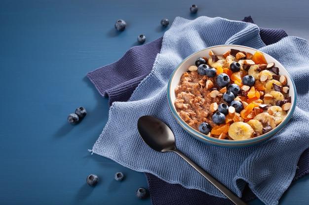 건강한 아침 식사를 위해 블루 베리, 견과류, 바나나, 말린 살구가 들어간 초콜릿 오트밀 죽