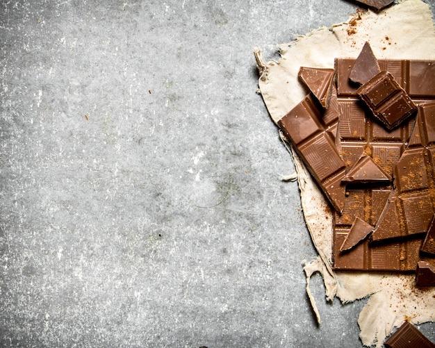 古い生地にチョコレート。石のテーブルの上。