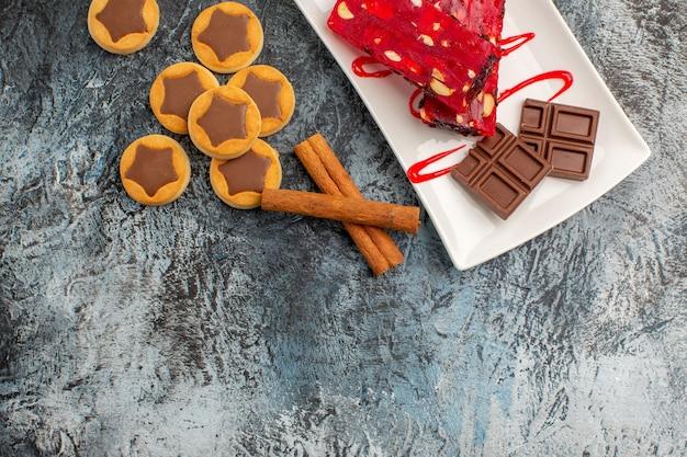 Шоколад на белой тарелке с печеньем и палочками корицы на серой земле