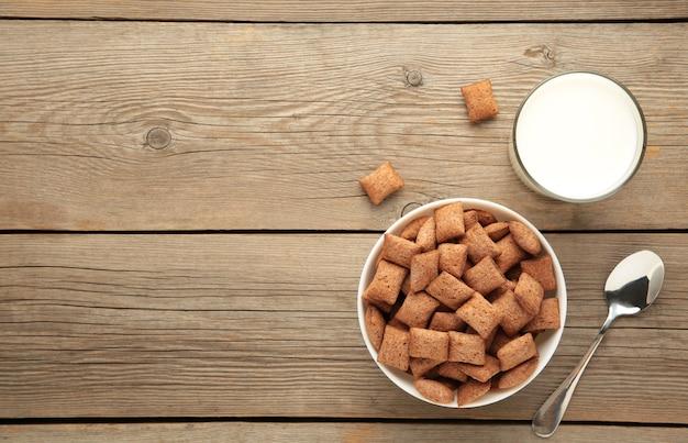 チョコレートは、青い背景にミルクとボウルにコーンフレークをパッドします。シリアルの質感。