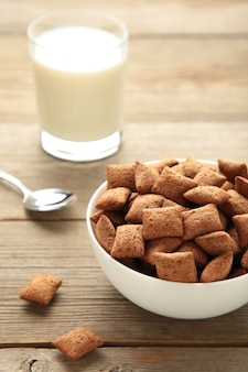 Chocolate pads corn flakes and milk in bowl on grey background. vertical photo