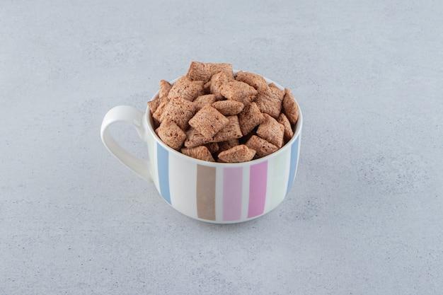 Chocolate pads cornflakes in ceramic mug on stone background. high quality photo