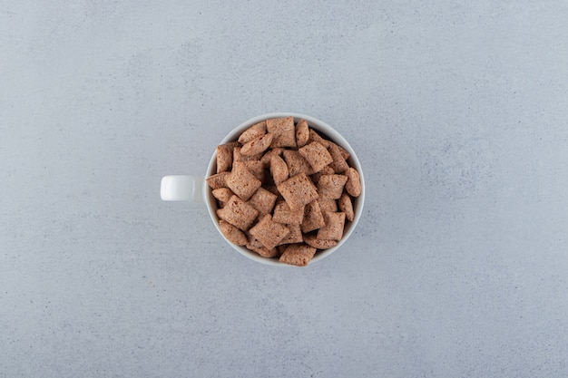 Fiocchi di mais in pastiglie di cioccolato in tazza di ceramica su superficie in pietra