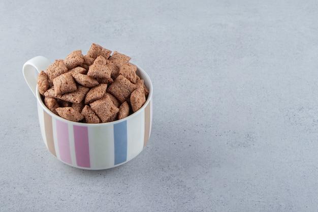チョコレートは、石の背景にセラミックマグカップのコーンフレークをパッドします。高品質の写真