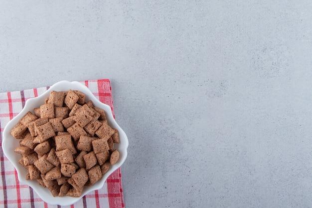 チョコレートは、石の背景に白いボウルにコーンフレークをパッドします。高品質の写真