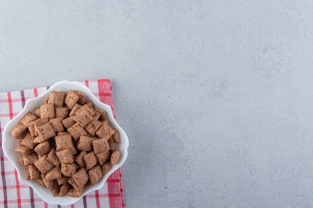 Chocolate pads cornflakes in white bowl on stone background. high quality photo