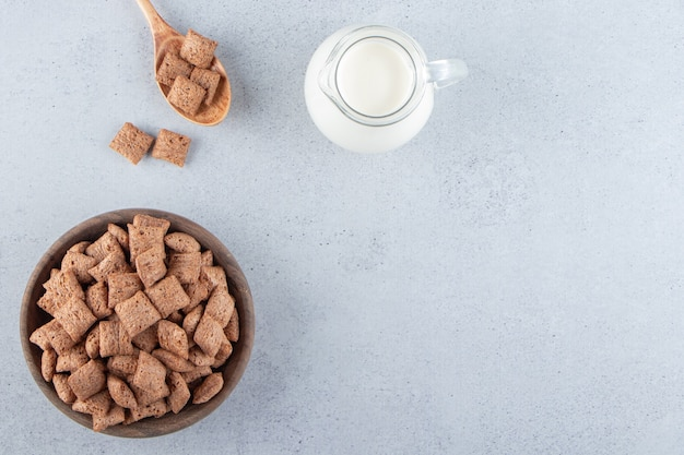 Chocolate pads cornflakes in wooden bowl with bottle of milk. high quality photo