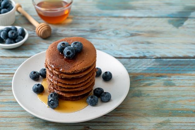 Blueberryies와 접시에 꿀 초콜릿 팬케이크 스택
