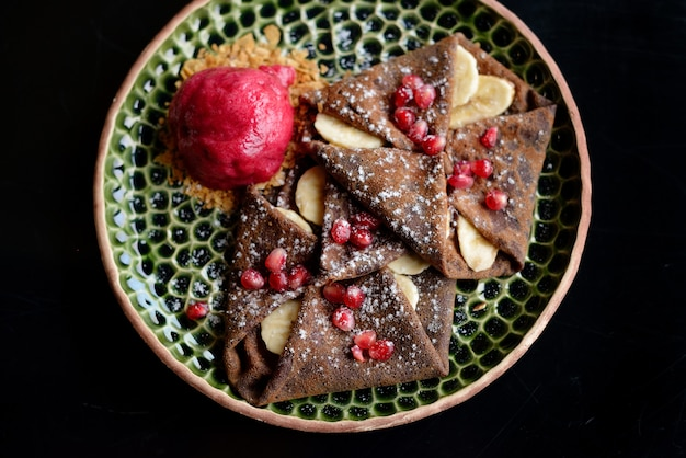 Chocolate pancake with bananas, pomegranate and sorbet