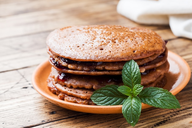 Chocolate pancakes with berry jam and mint for breakfast on wooden table