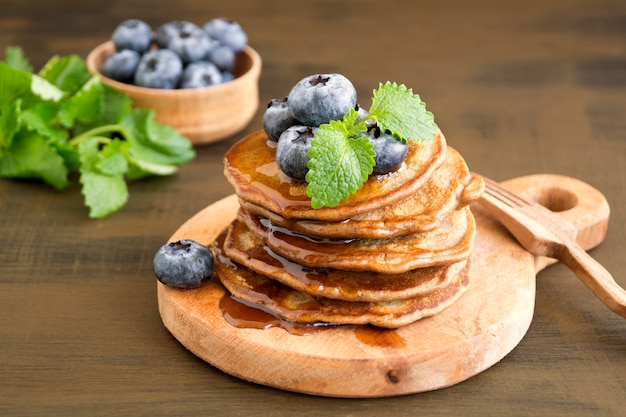 Chocolate pancakes with blueberries on a dark background.