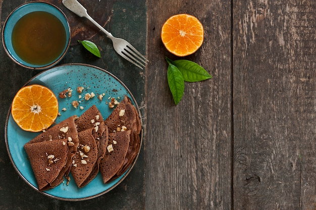 Chocolate pancakes with oranges on blue plate with cup of tea on wooden table