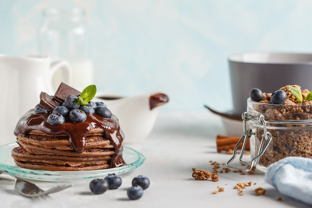 Chocolate pancakes with syrup and berries, chocolate granola and milk. breakfast concept, blue background
