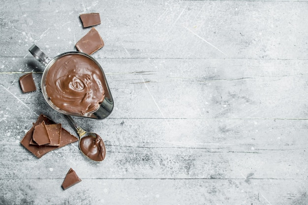 Chocolate paste in bowl. on a rustic background.