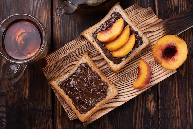 暗い木の背景、甘いスナックのまな板の上にお茶を入れたプレートに桃のスライスとチョコレートペーストトースト。
