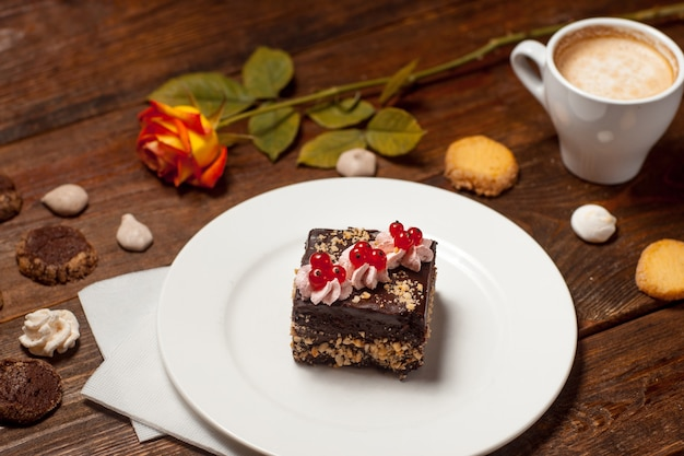 Chocolate pastry cake cup of cappuccino on festive wooden table