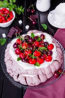 Chocolate pavlova cake with whipped cream and cherries. australian and new zealand cuisine.