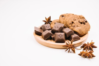 Chocolate pieces and cookies with star anise on wooden frame against white background