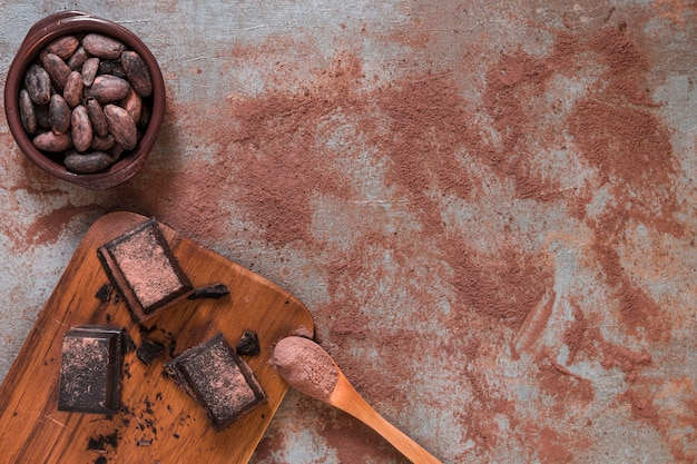 Chocolate pieces on chopping board and bowl of cocoa beans