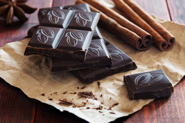 Chocolate pieces and cinnamon on wooden background