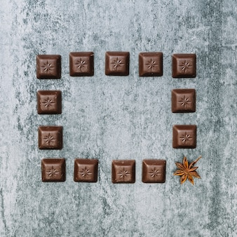 Chocolate pieces frame with one star anise on an old wall