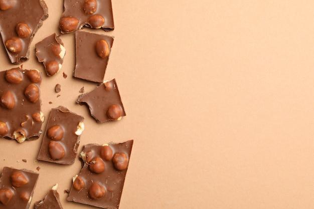 Кусочки шоколада на бежевом, вид сверху. сладкая еда