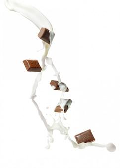 Chocolate pieces and splashes of milk Premium Photo