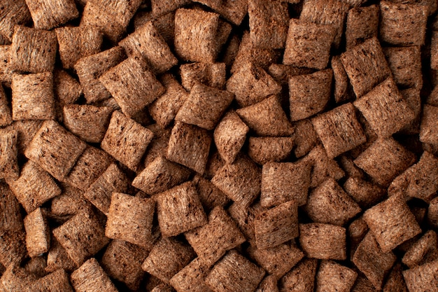 Chocolate pillows background texture. brown choco cereal pads.