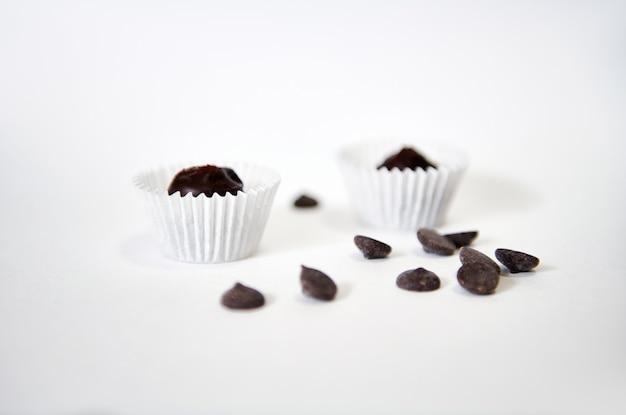 白い表面に分離された包装紙のチョコレートの丸薬とプラリネ