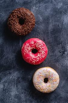Шоколадные, розовые и ванильные пончики с посыпкой в ряд, сладкая глазированная десертная еда на темном бетонном текстурированном столе, вид сверху