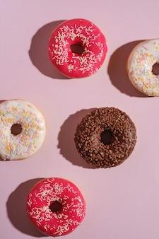 Шоколадные, розовые и ванильные пончики с посыпкой, сладкая глазированная десертная еда на розовом минимальном фоне, вид сверху