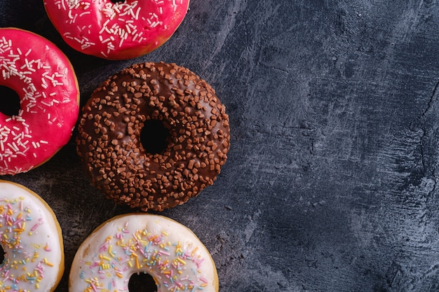 Chocolate, pink and vanilla donuts with sprinkles, sweet glazed dessert food on dark concrete textured background, top view copy space