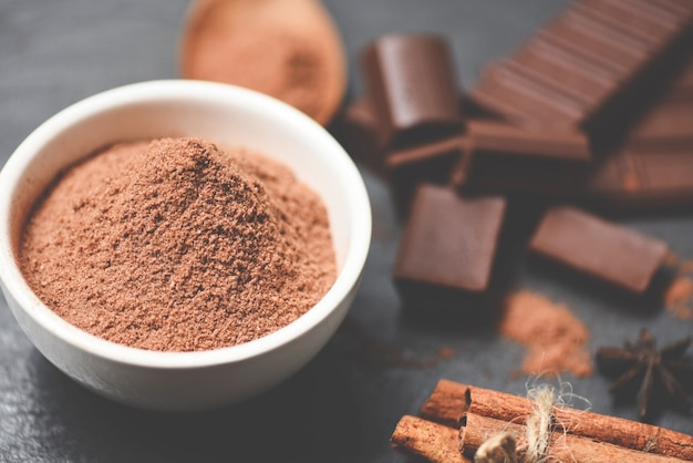 Chocolate powder on bowl and candy sweet dessert for snack chocolate bar and spice on dark background , selective focus