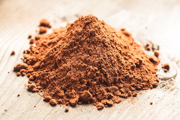 Куча шоколадного порошка на деревянном фоне