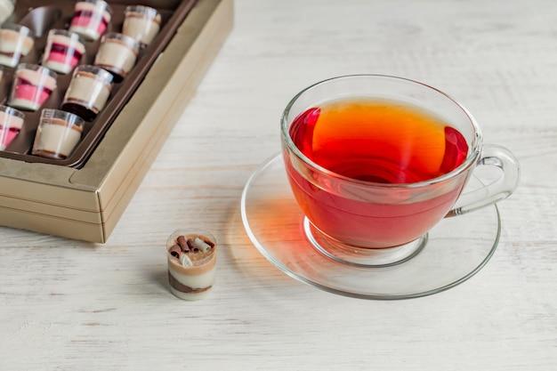 チョコレートプラリネcanidiesと白い木製の背景に紅茶のカップ