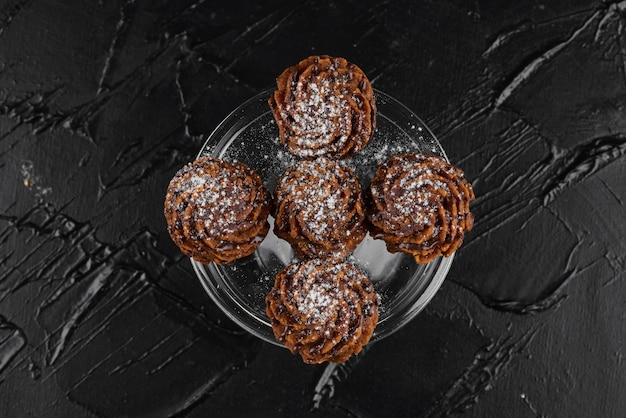 Praline di cioccolato su superficie nera.