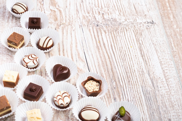 Chocolate pralines on wood, text space