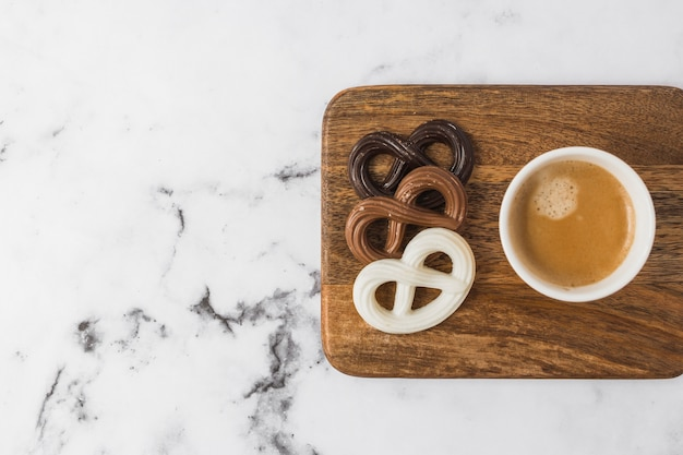 Chocolate pretzels and coffee cup on chopping board over marble textured background