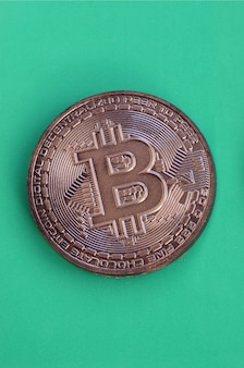 Chocolate product in the form of physical bitcoin lies on a green plastic background