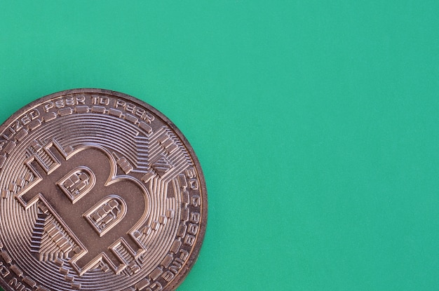 Chocolate product in the form of physical bitcoin lies on a green plastic background.