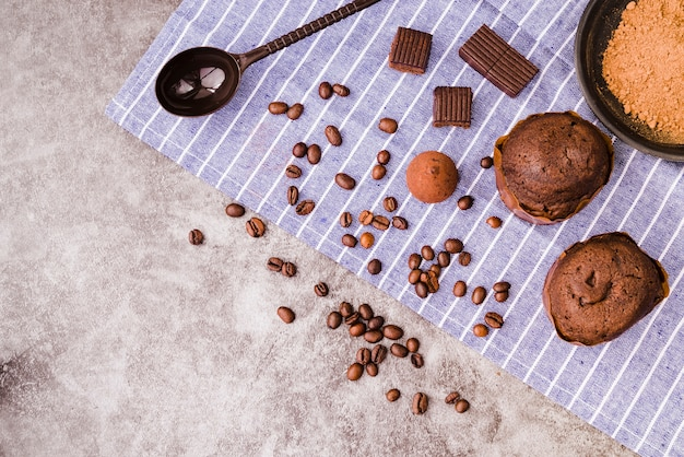 Chocolate products and ingredients on napkin over the concrete backdrop